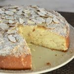 Almond Ricotta cake with slice almonds and powdered sugar on top.
