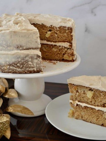 Apple Spice Cake with Cinnamon Buttercream Frosting on a white pedestal with a slice on another white plate.
