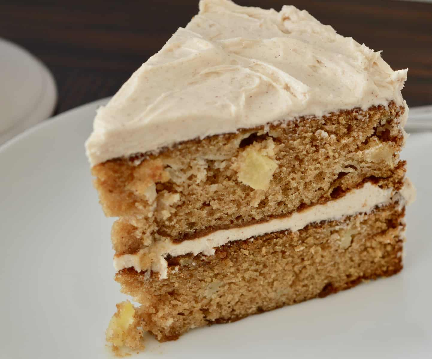 Slice of Apple Spice Cake with Cinnamon Buttercream Frosting on a white plate.