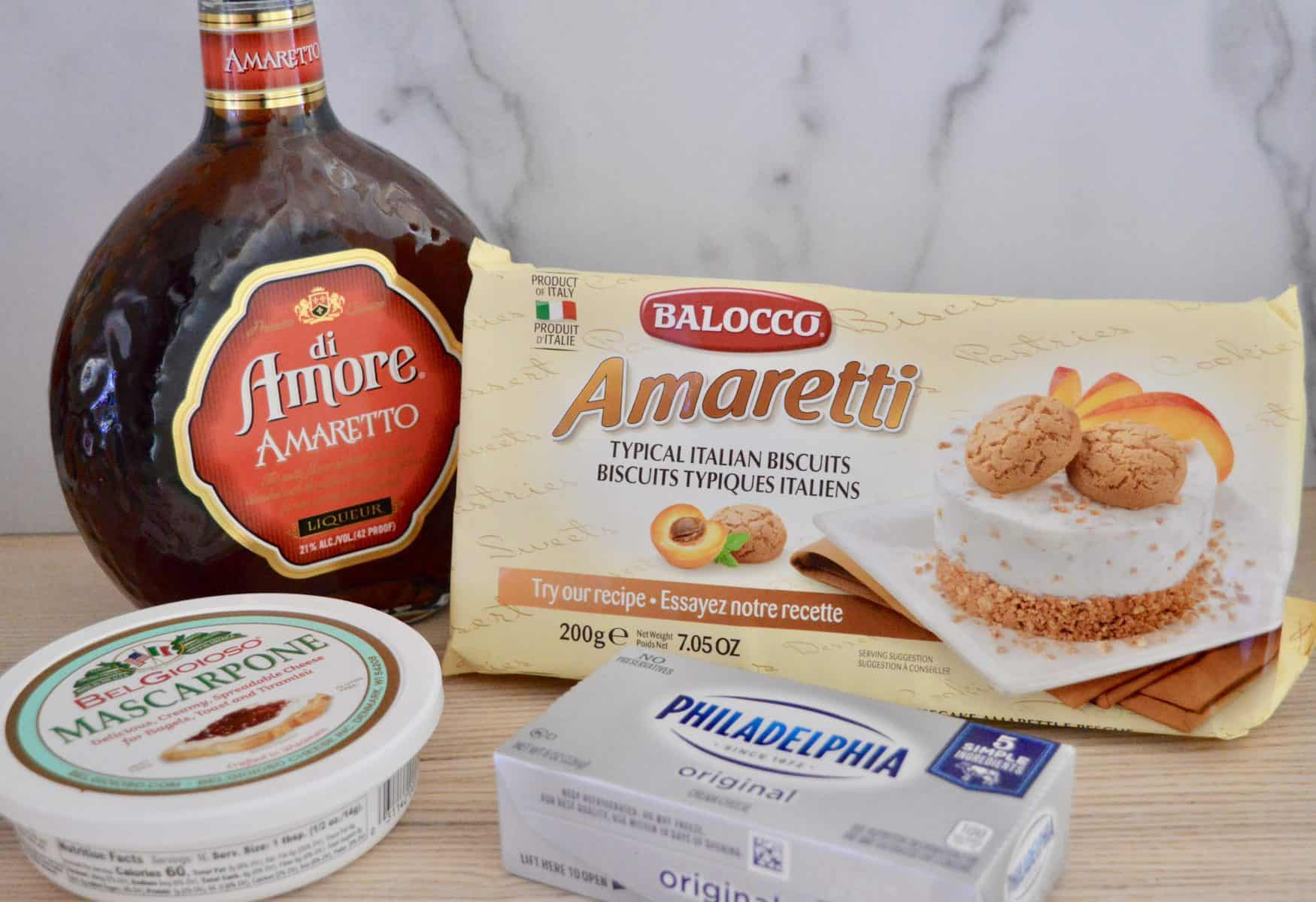 amaretti cookies, amaretto liqueur, mascarpone cheese, and cream cheese on a counter.