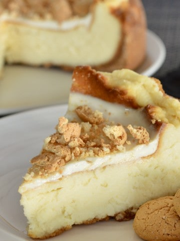 Amaretto Mascarpone Cheesecake on a plate with amaretti cookies.
