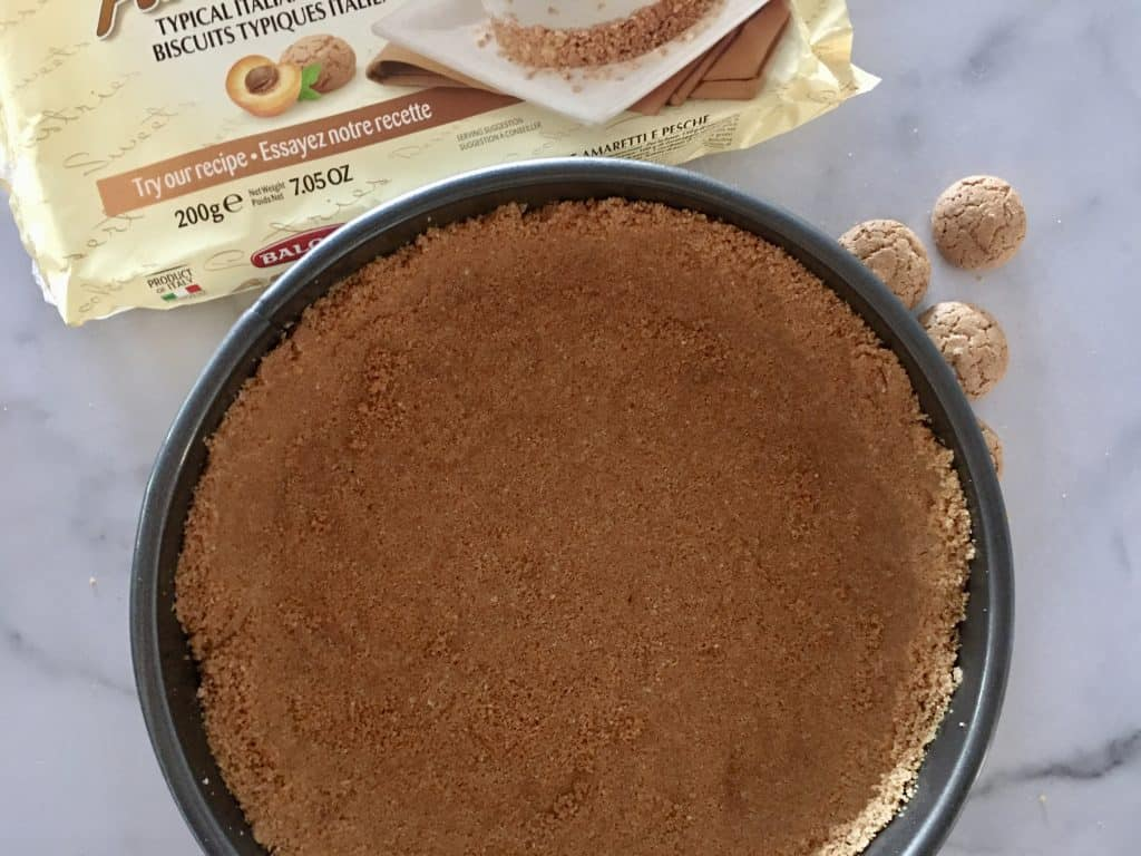 Amaretti cookie cheesecake crust in a springform pan.
