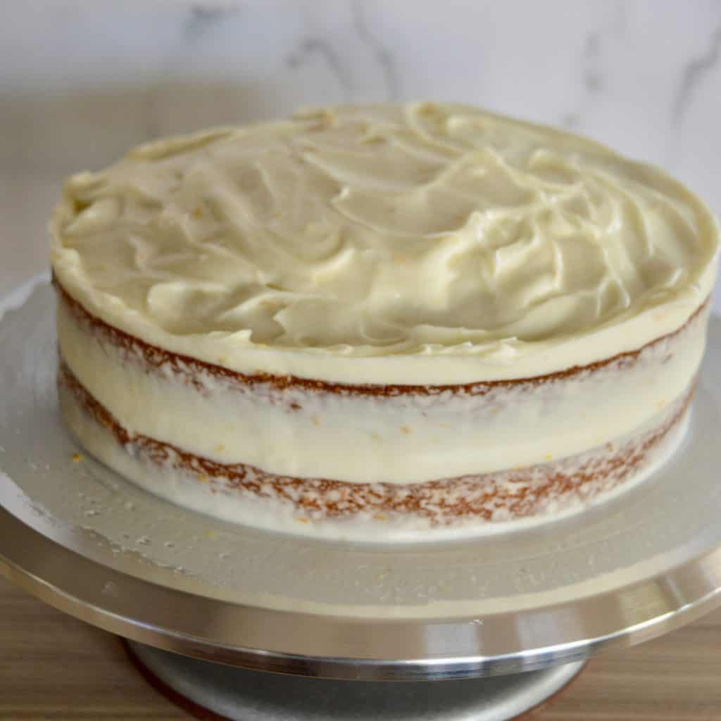 naked cake frosting on cake turntable.