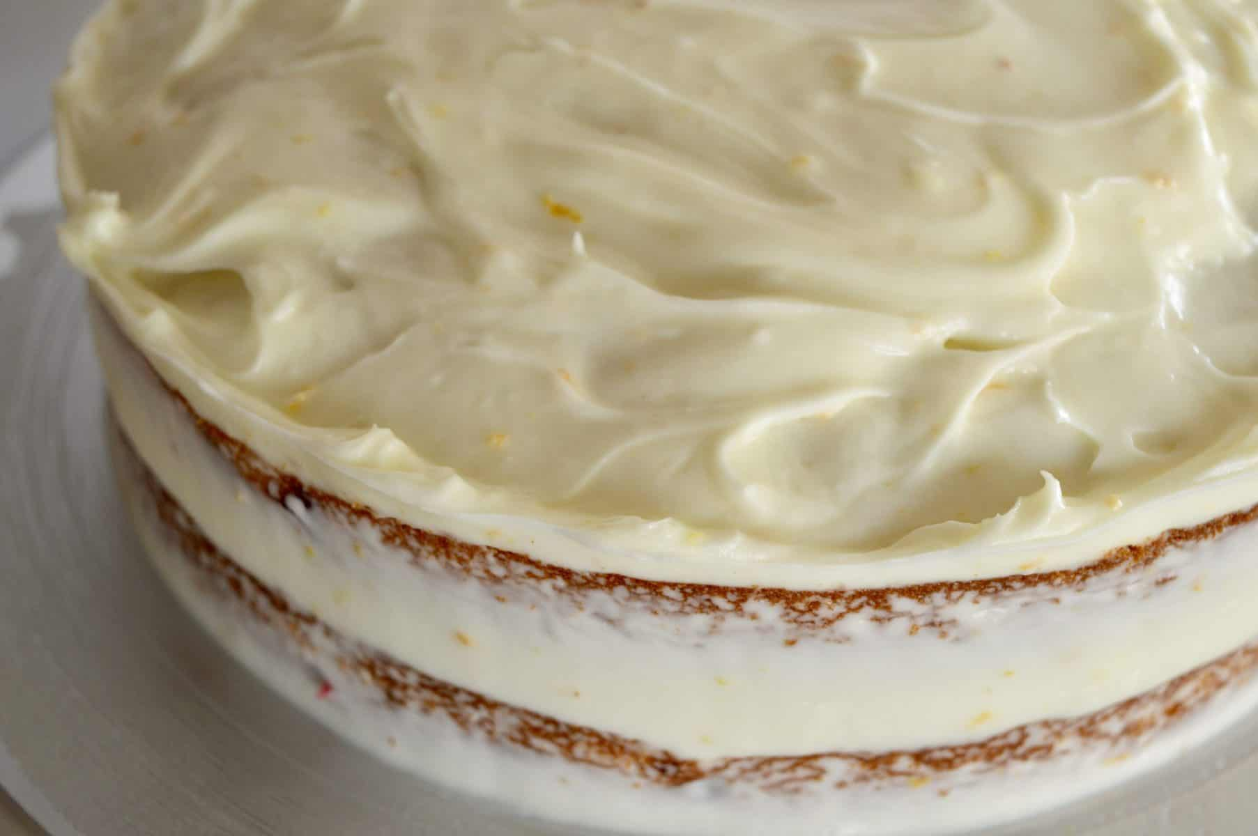 Close up of orange cream cheese frosting on the cake.