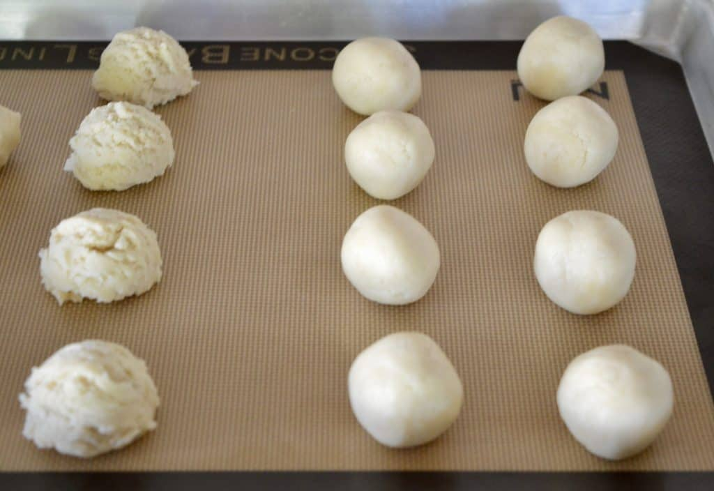 rolling dough into balls on baking mat.