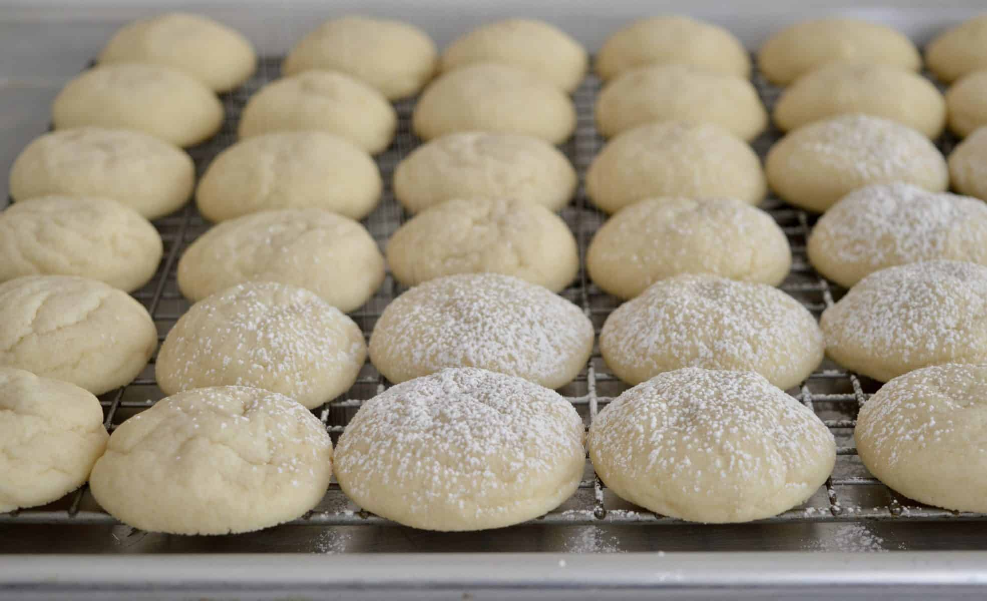 Greek Butter cookies getting dusted with powdered sugar.