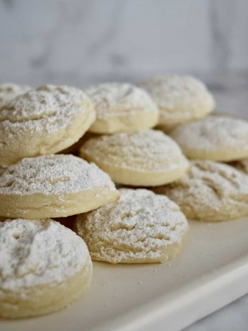 Greek butter cookies stacked on a white plate.