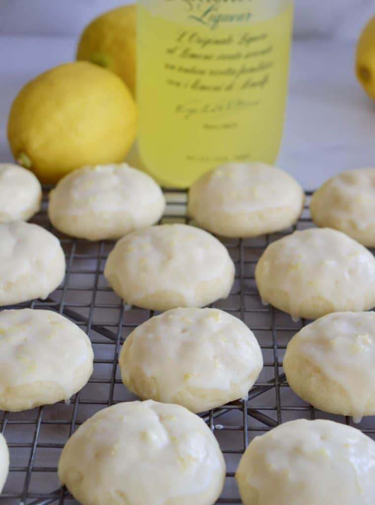 Limoncello Ricotta Cookies on a wire baking rack with limoncello liqueur in the background.