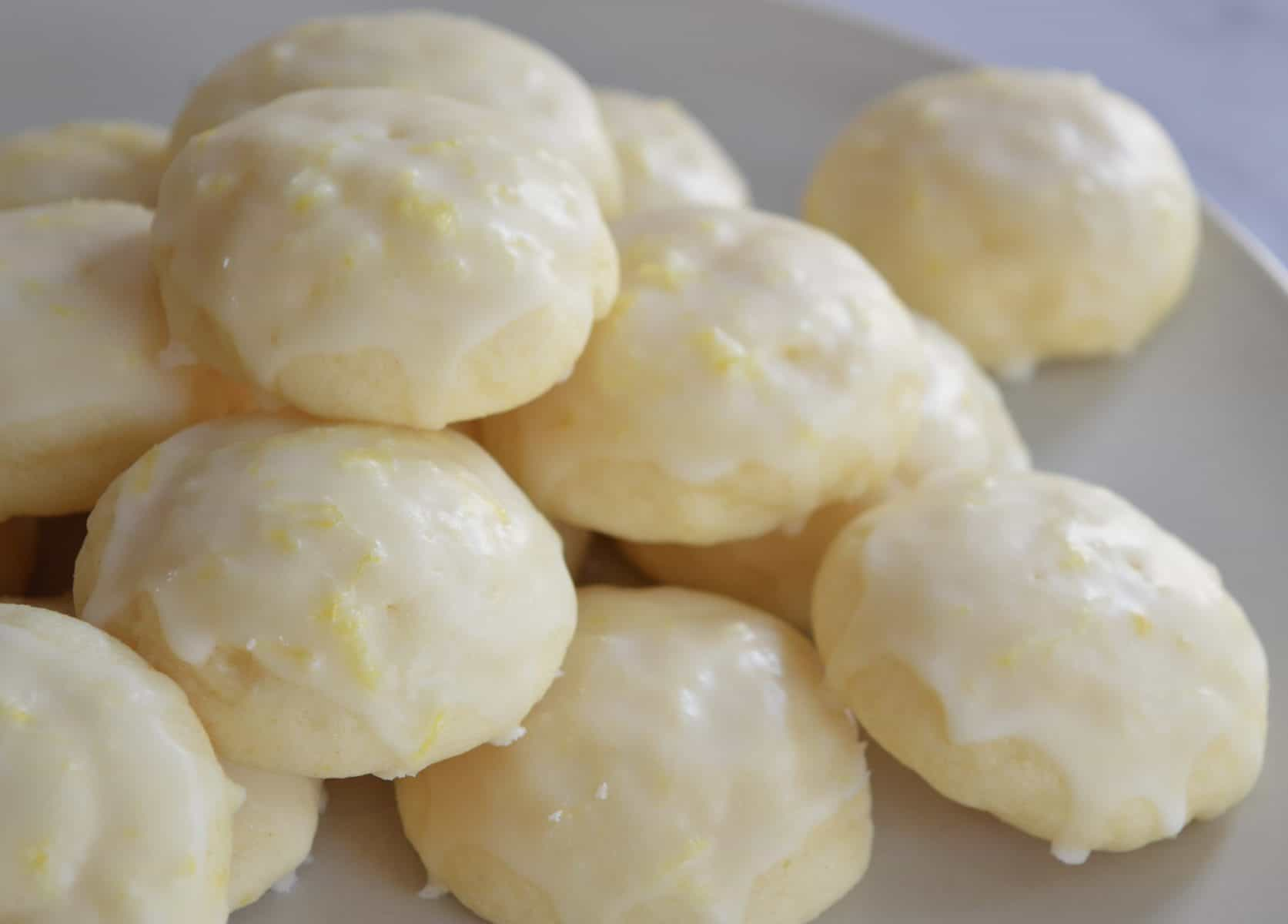 Limoncello Ricotta Cookies stacked on a white plate.