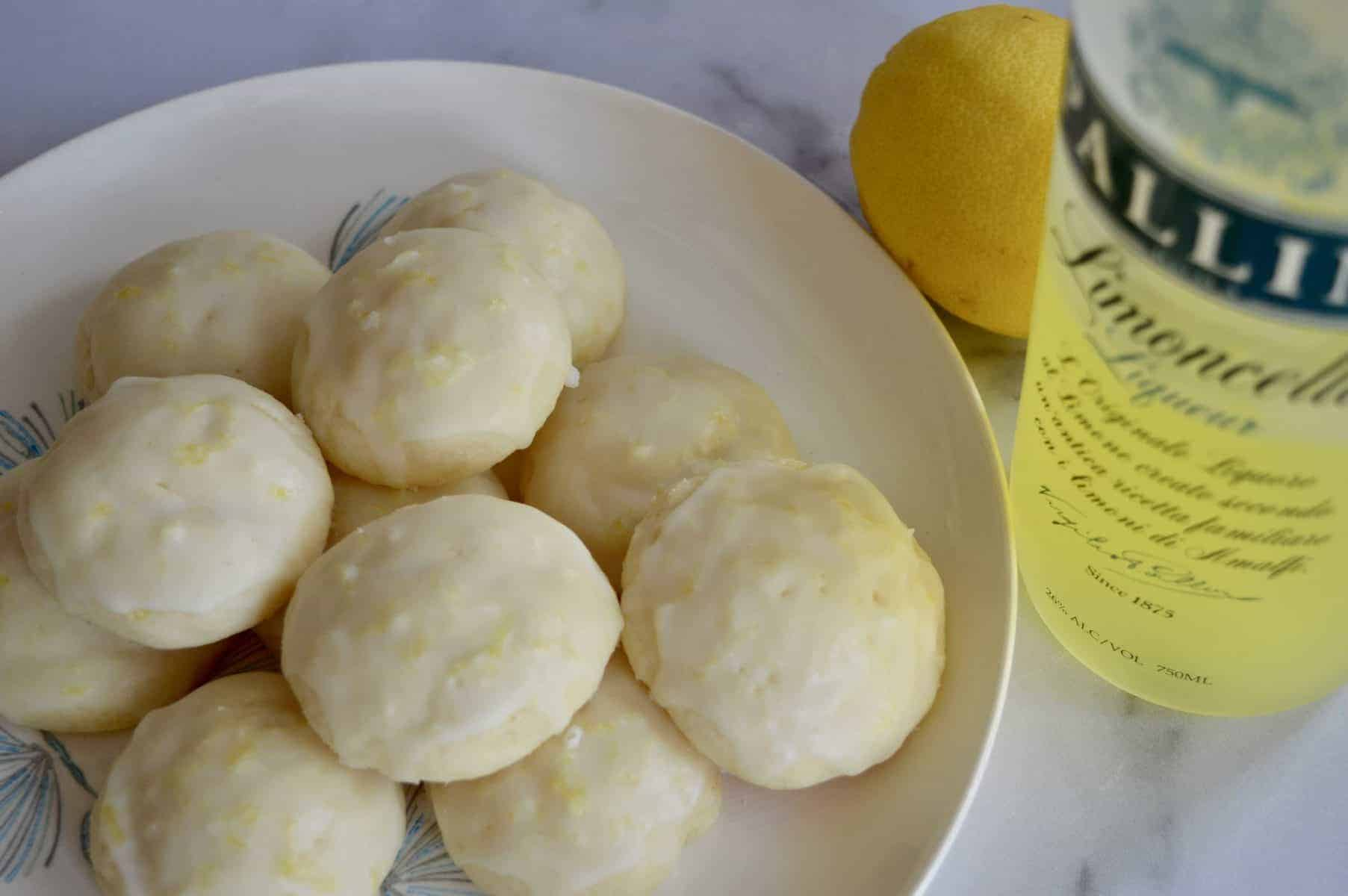 Limoncello Ricotta Cookies on a plate with Limoncello liqueur.