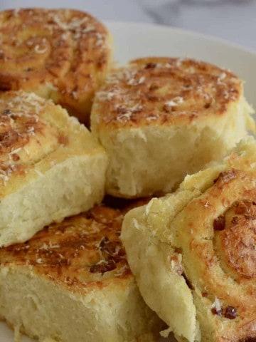 pinwheel bread rolls on a white serving platter.