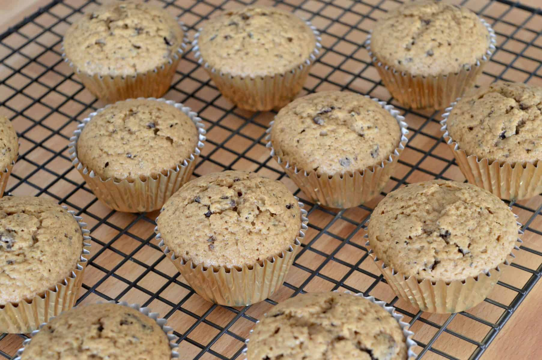 muffins in gold liners cooling on a wire cooling rack.