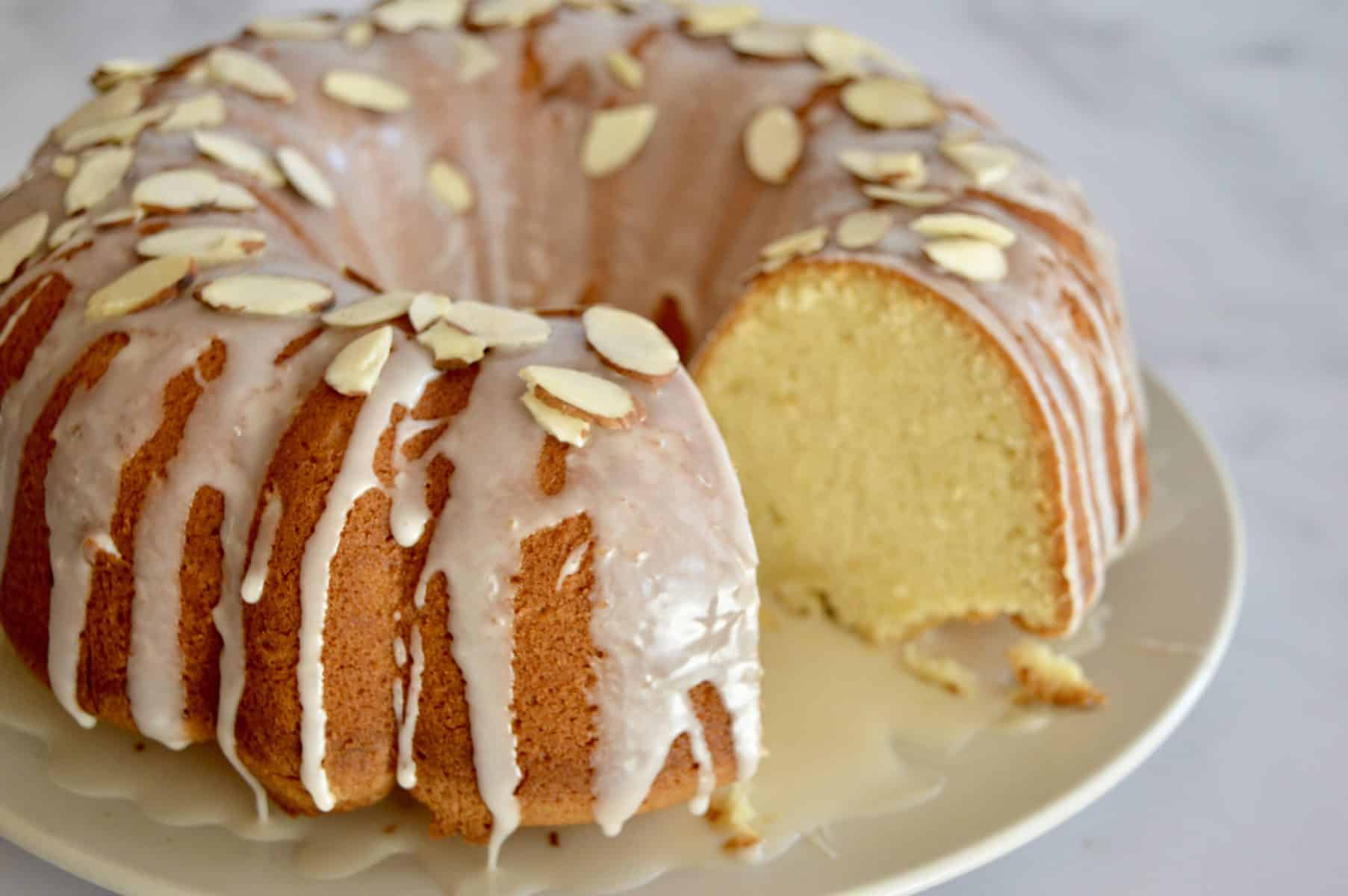 frosted bundt cake with almonds on top.