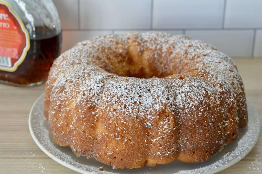 Bundt on plate with powdered sugar sprinkled on top.