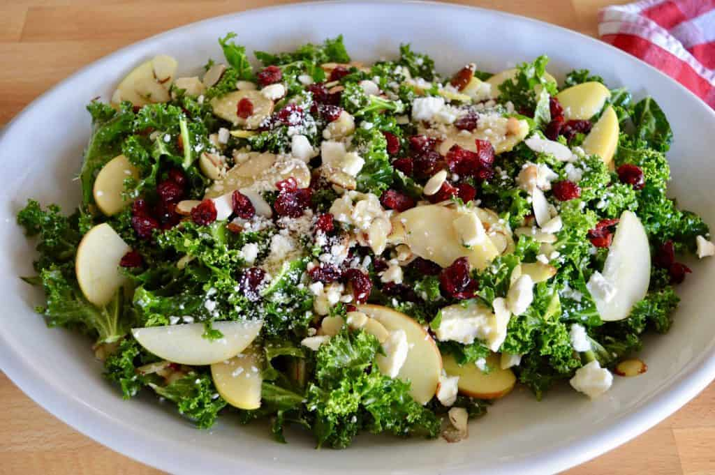 Overhead photo of kale cranberry feta salad in a white oval platter.