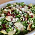 Kale Cranberry Feta Salad with almonds and apples in a white serving platter.