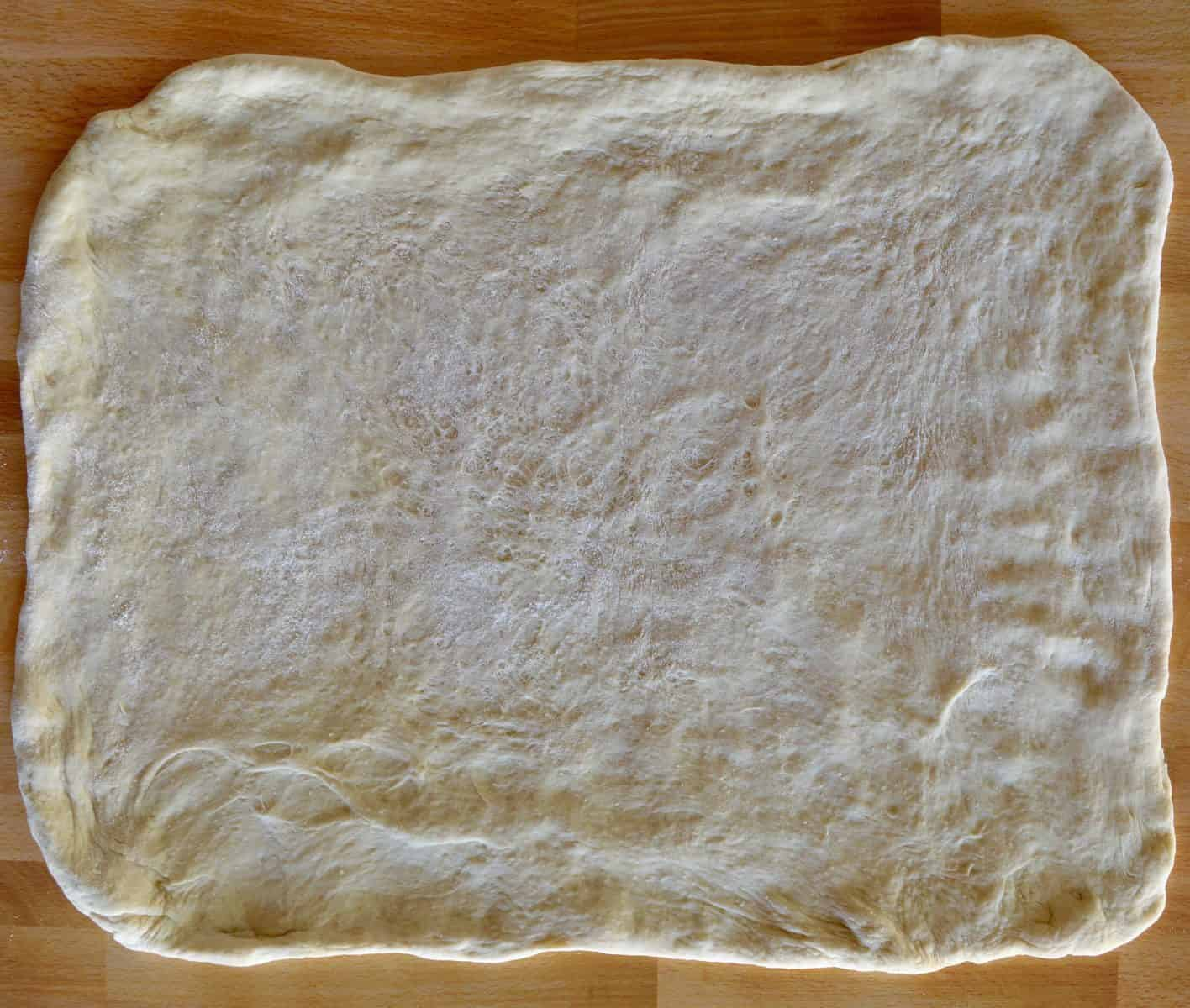 Stromboli dough rolled out into large rectangle.