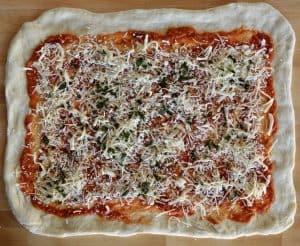 mozzarella and parmesan sprinkled over the Stromboli dough.