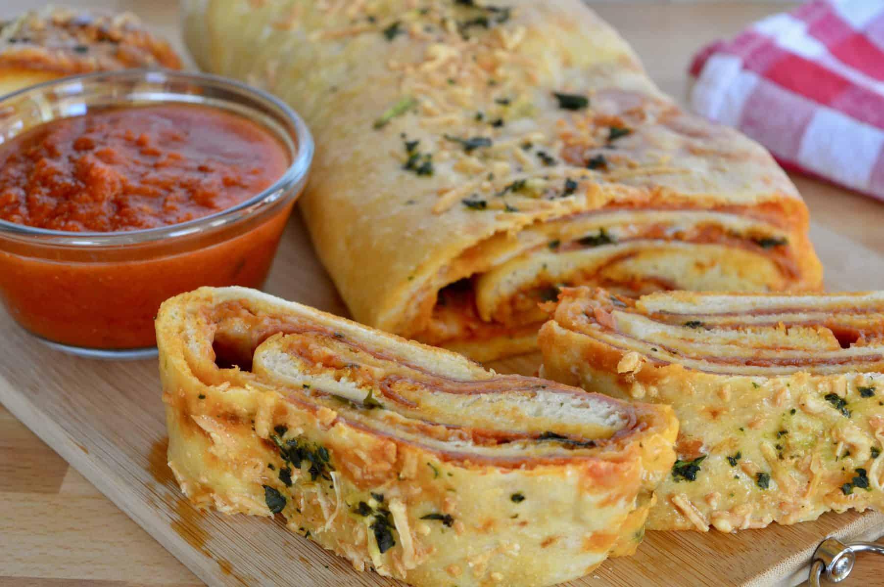 Italian Stromboli Recipe on a cutting board with marinara sauce for dipping.