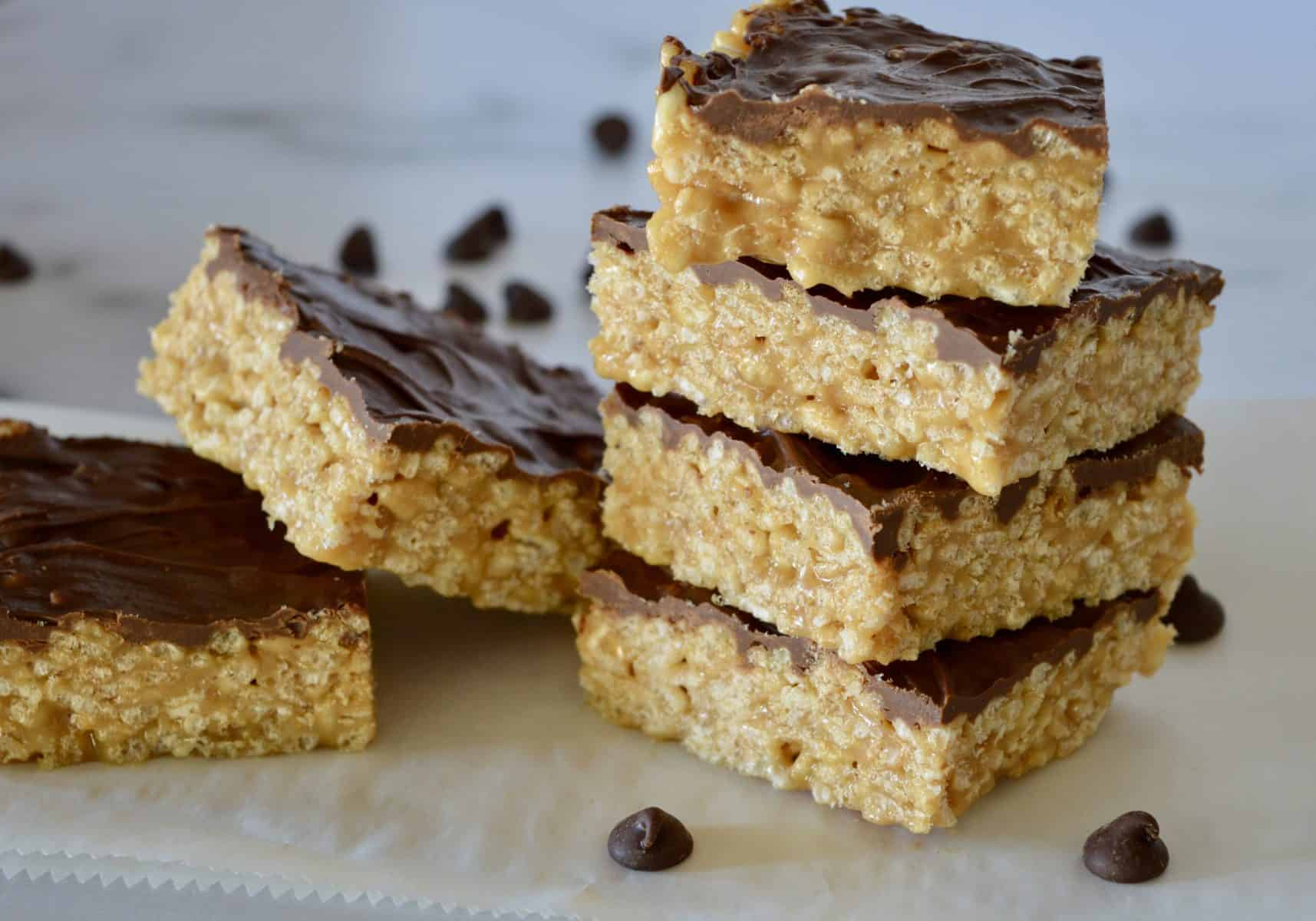 Caramel Peanut Butter Krispies staked on a white countertop.
