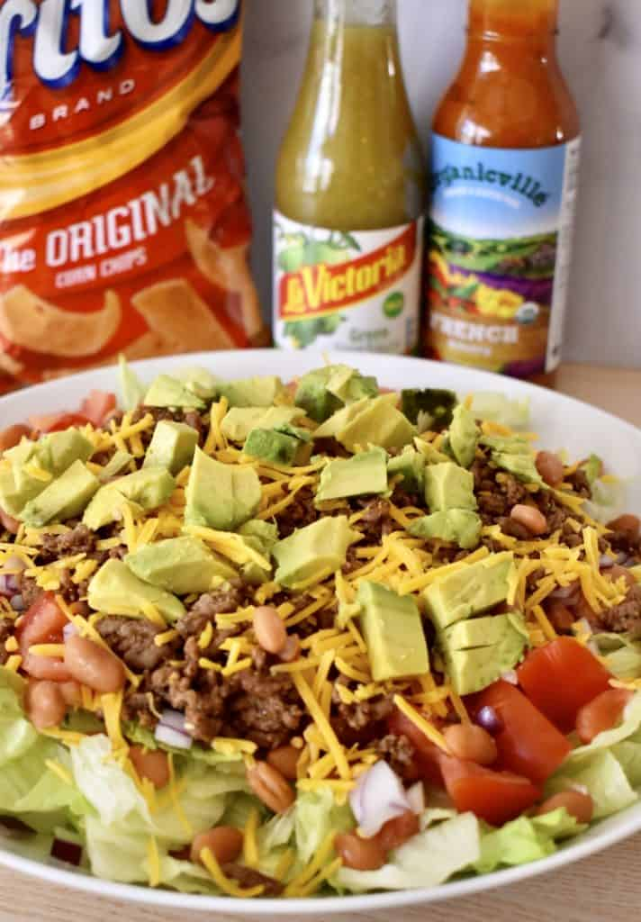 Chips and dressing located behind a picture of the salad.