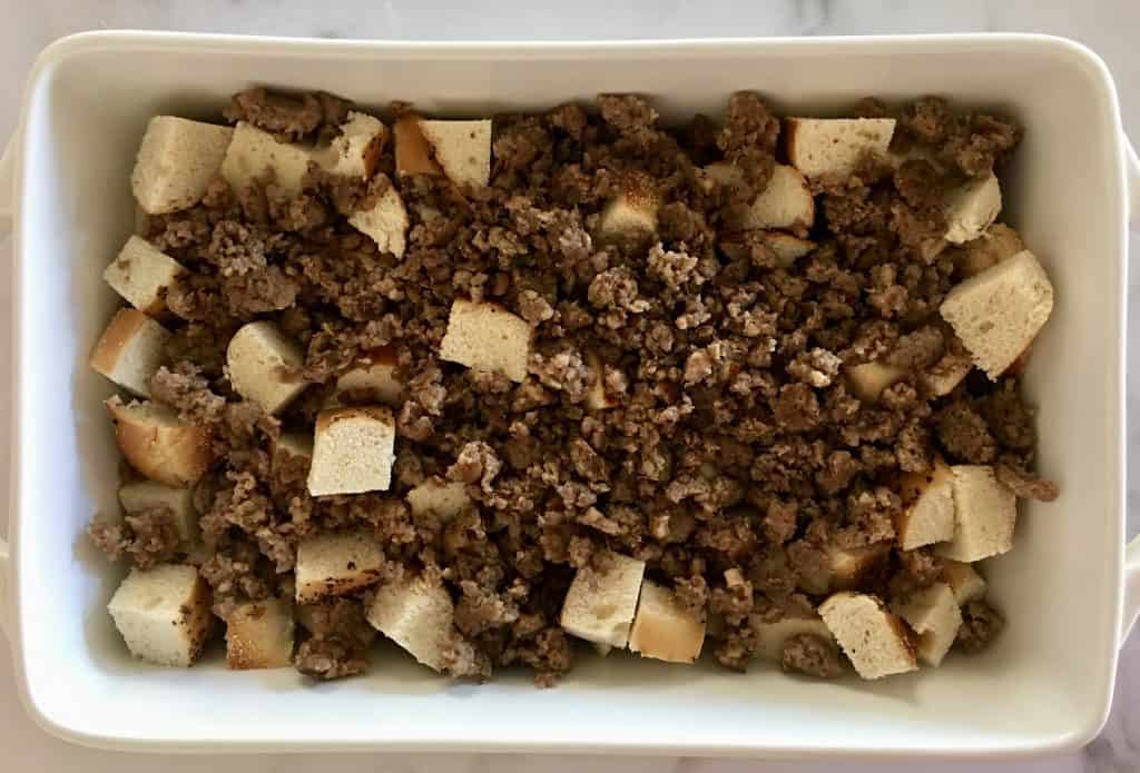 Cut up bread and cooked meat in a white casserole dish.