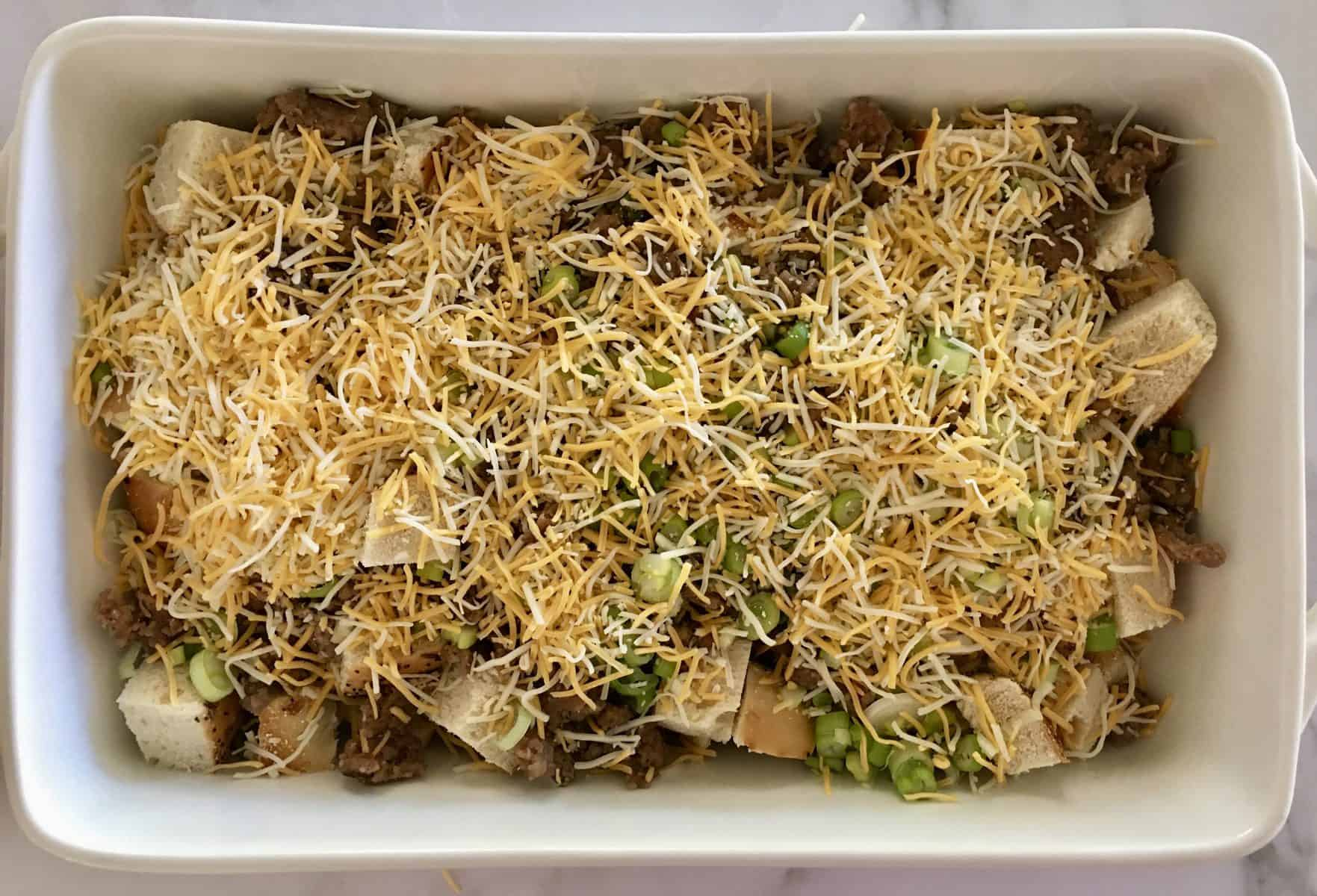 Breakfast Casserole filled with bread, meat, green onions, and cheddar cheese.