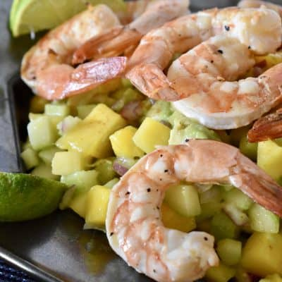 Shrimp mango cucumber salad on a plate with lime wedges.