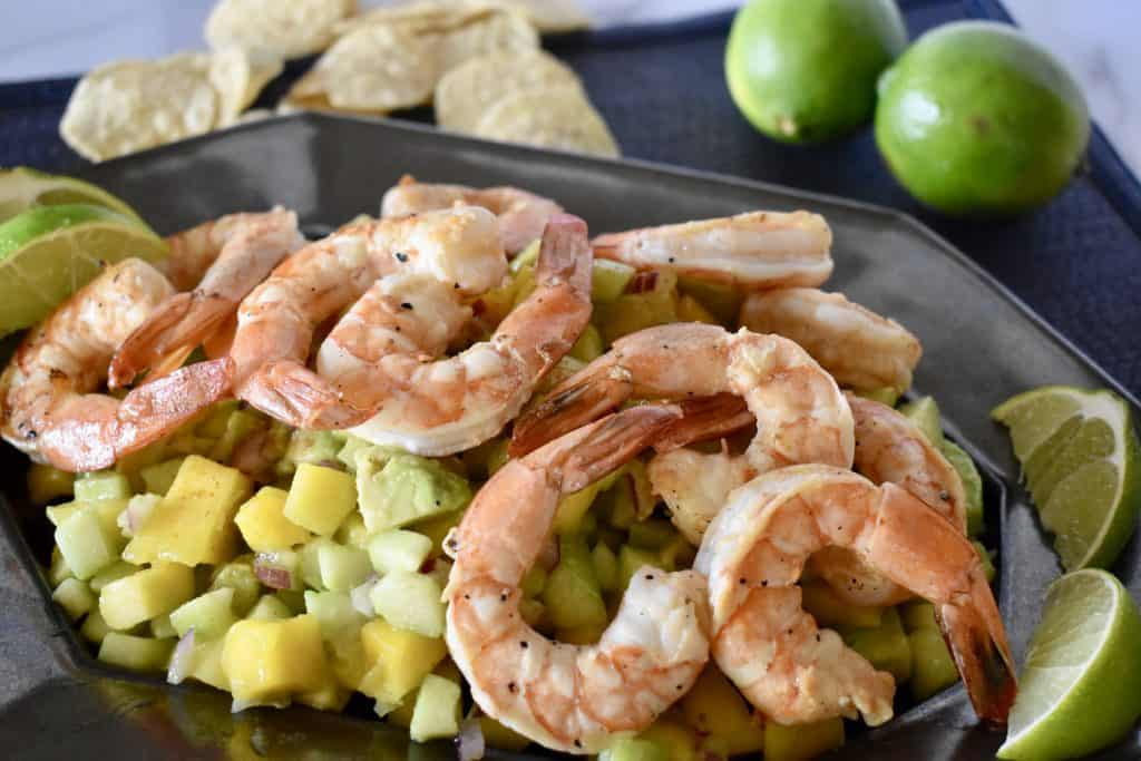 Shrimp on a bed of mango cucumber salad with tortilla chips it the background.