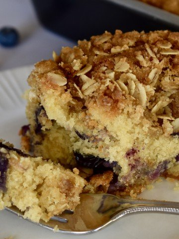 Blueberry Ricotta Coffee Cake on a white plate with a fork.