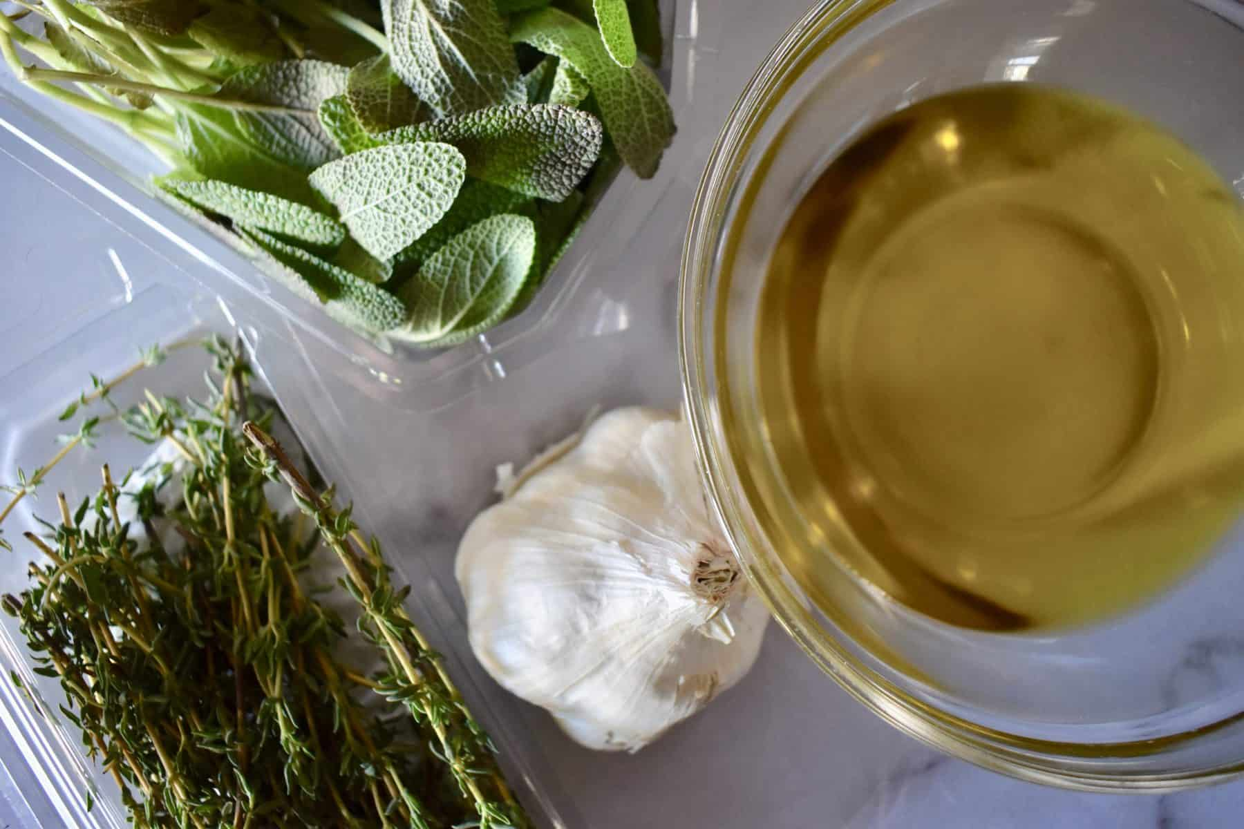 Garlic, thyme, sage, and olive oil on a countertop.