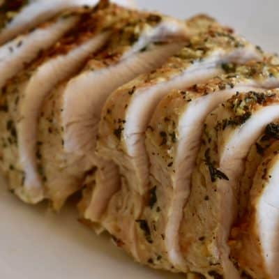 Slow cooker turkey breast cut into slices on a white plate.