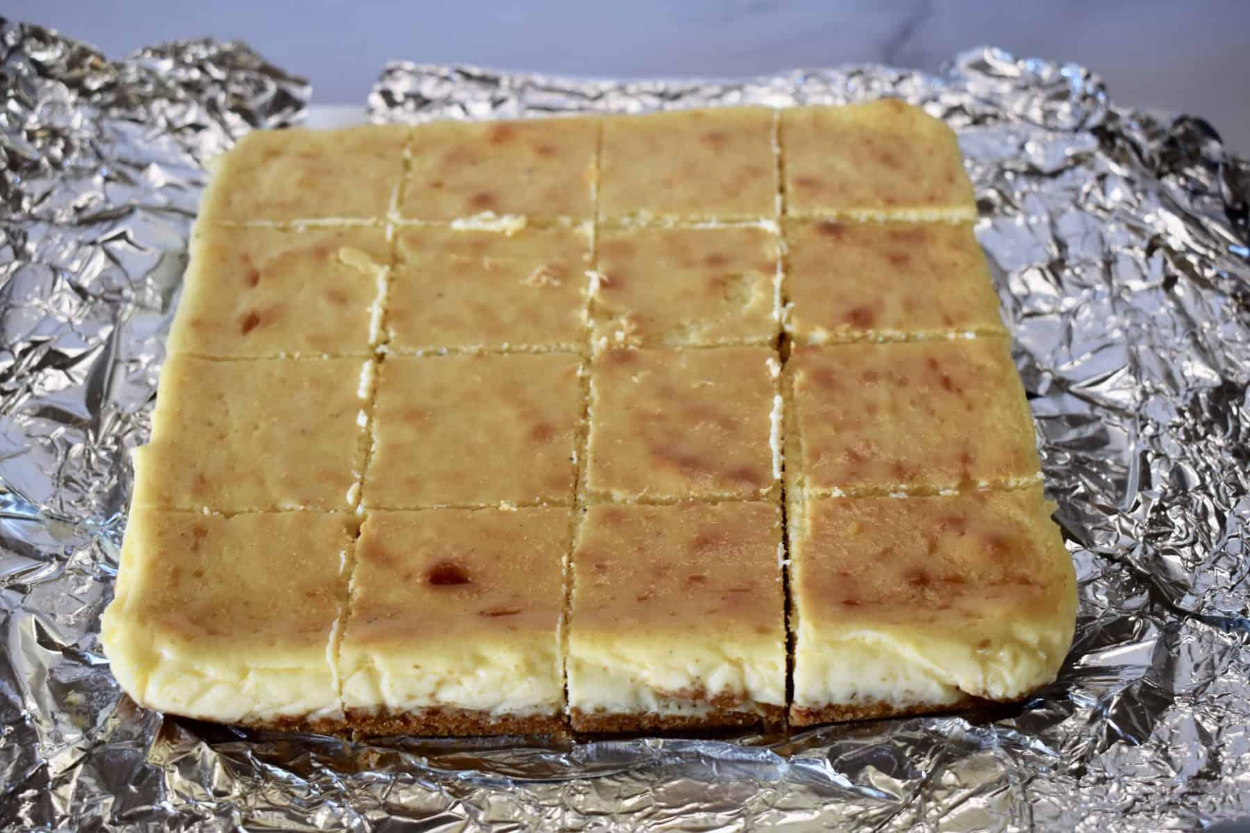Sliced Eggnog Cheesecake Bars on foil.