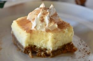 eggnog cheesecake bars with whipped cream on top.