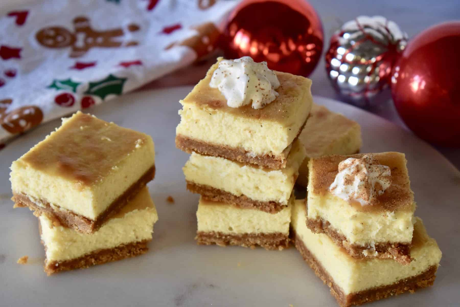 Eggnog Cheesecake Bars on a serving tray with red ornaments in the background.
