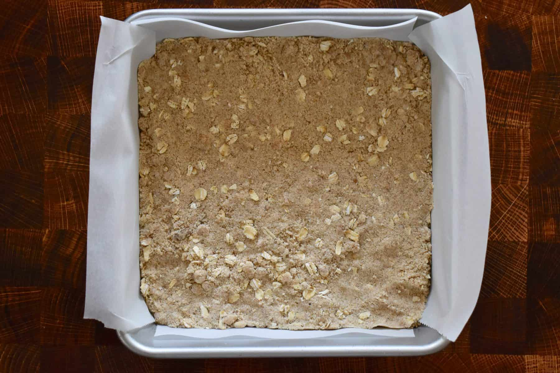 dough firmly pressed into a lined baking pan.