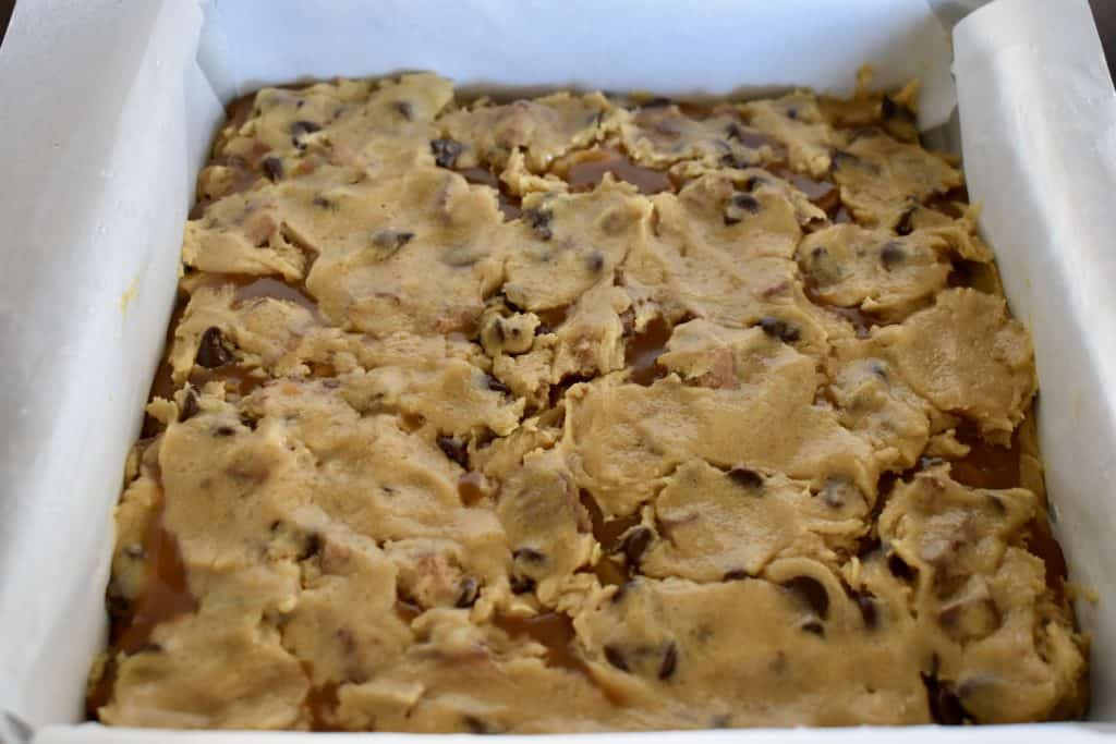 batter pressed over the caramel layer of the bars.