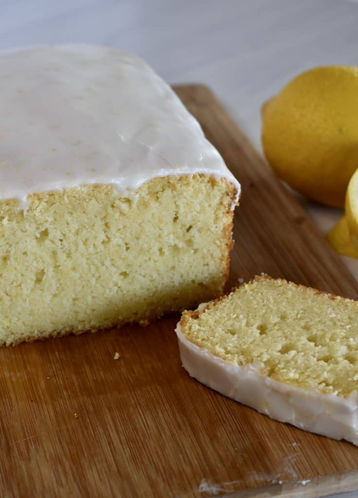 Lemon Ricotta Pound Cake on a wood cutting board with a lemon in the background.