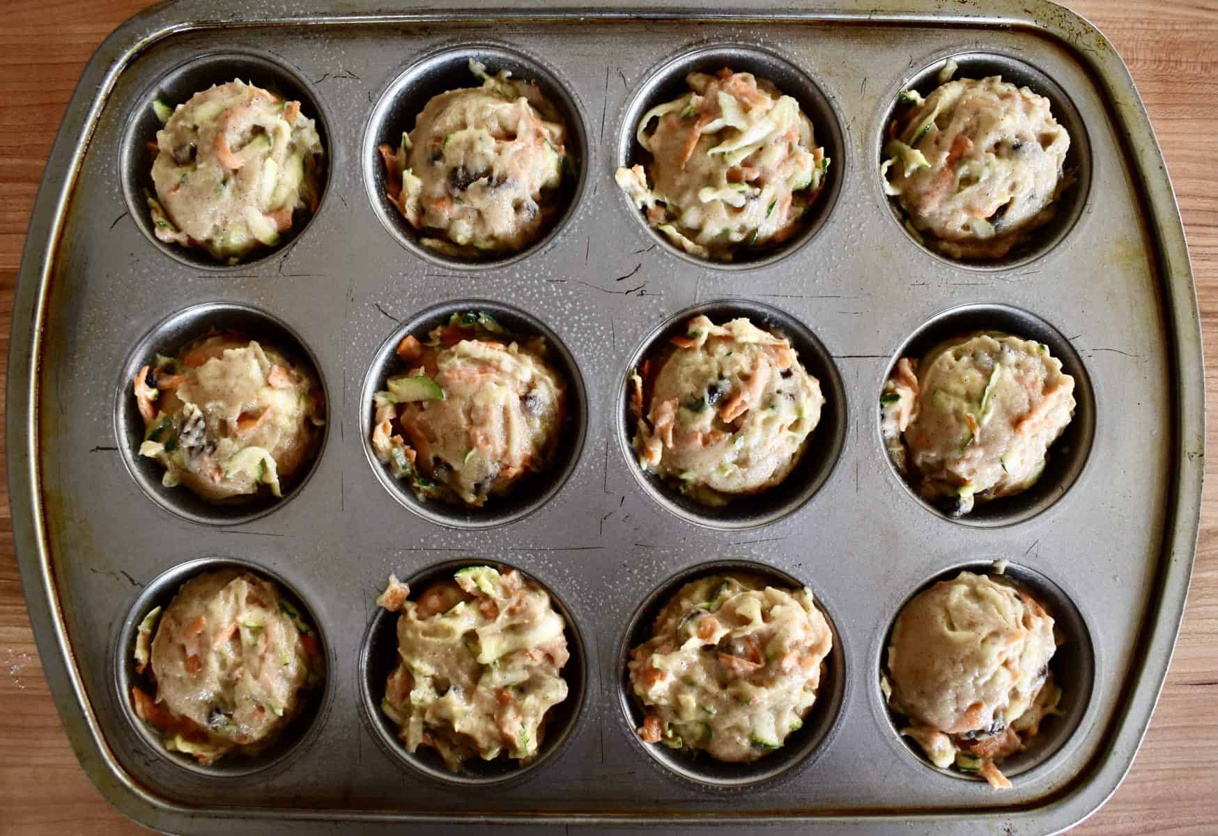 muffin tins filled with zucchini carrot raisin muffin batter.