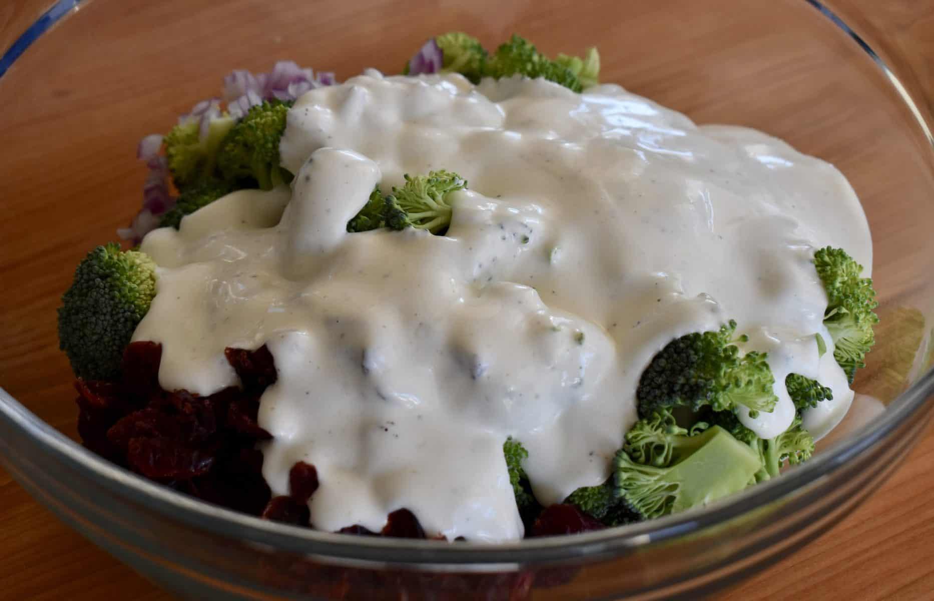 greek yogurt dressing poured over broccoli cranberry salad in a large glass bowl.