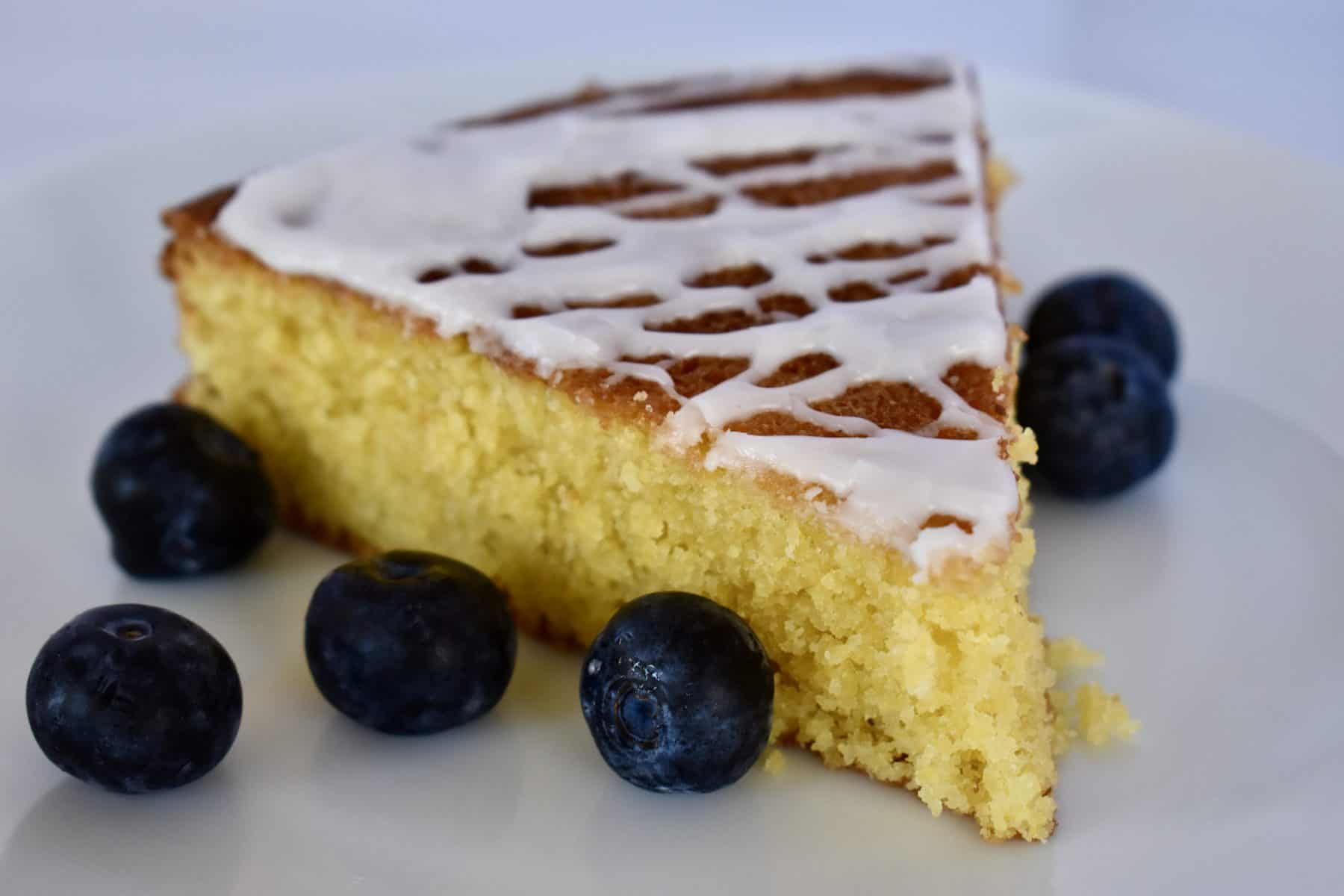 Lemon Polenta Cake on a plate with blueberries.