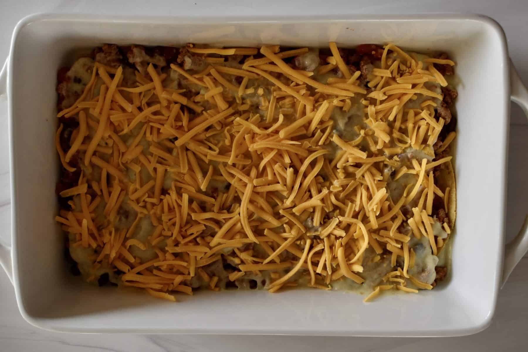 shredded cheddar on top of the green enchilada sauce layer.