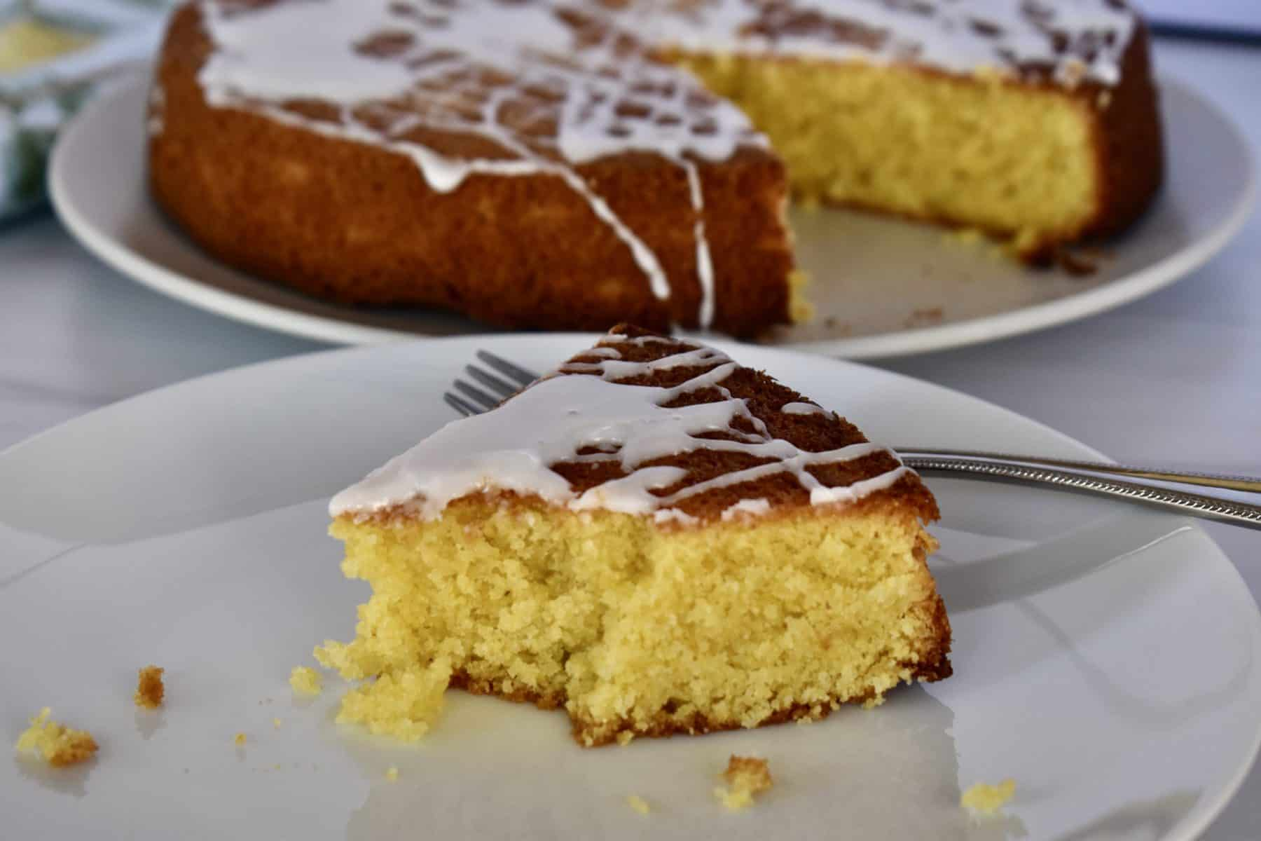 Lemon polenta cake on a white plate with a fork.
