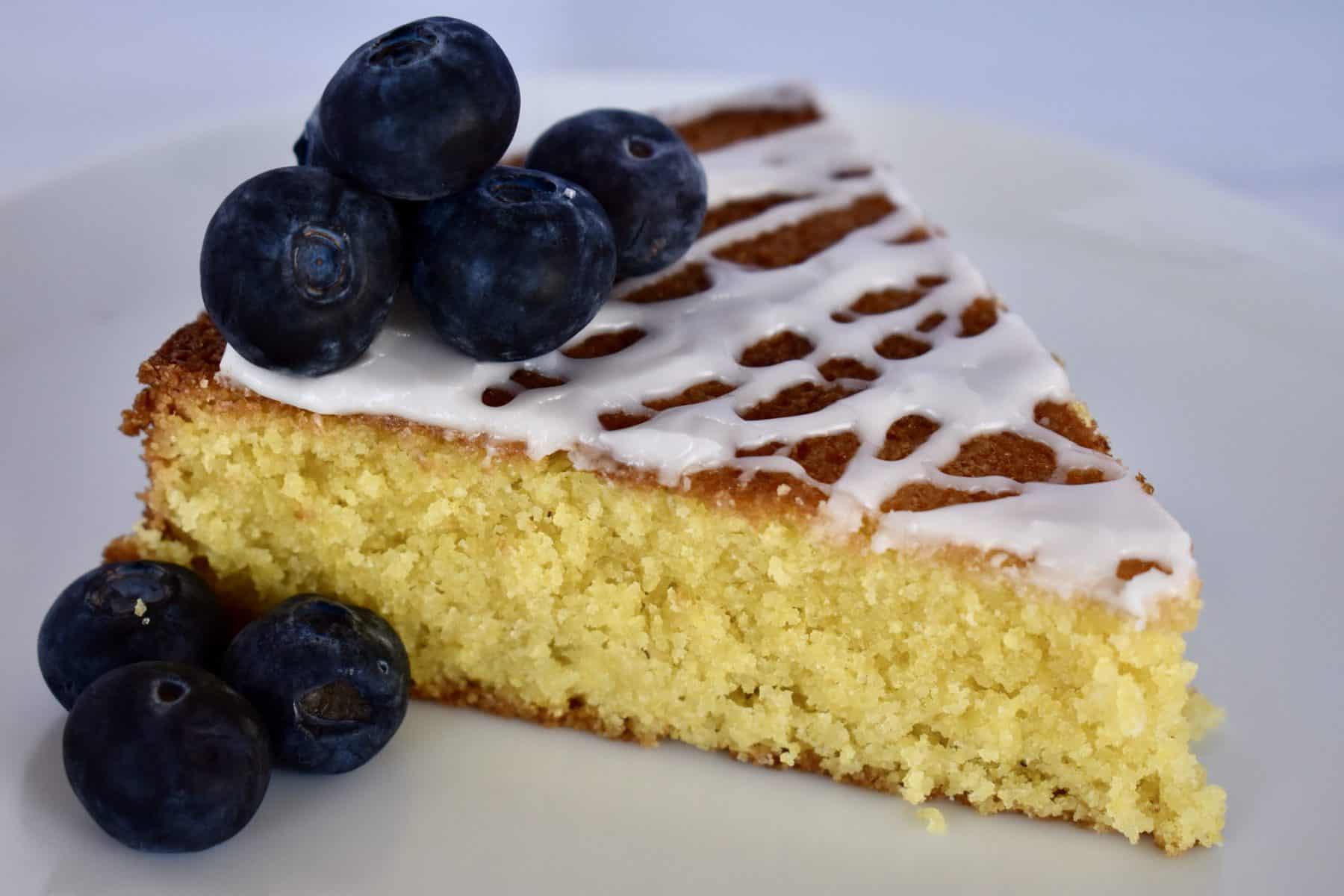 Lemon Polenta Cake on a white plate with blueberries.