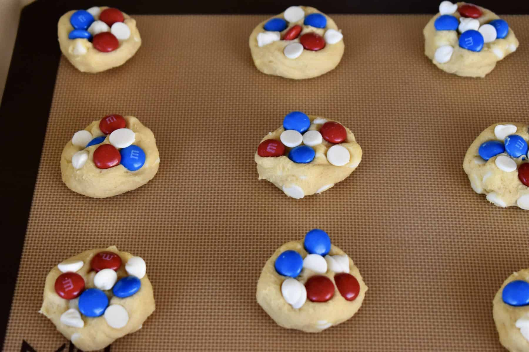 Cookies on a baking sheet with red and blue M&M's pressed into them.