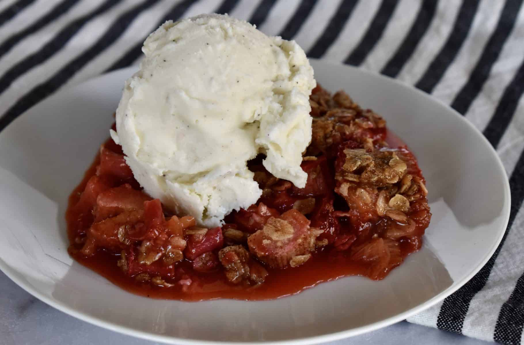 Strawberry Rhubarb Crisp on a white plate with a scoop of vanilla ice cream.