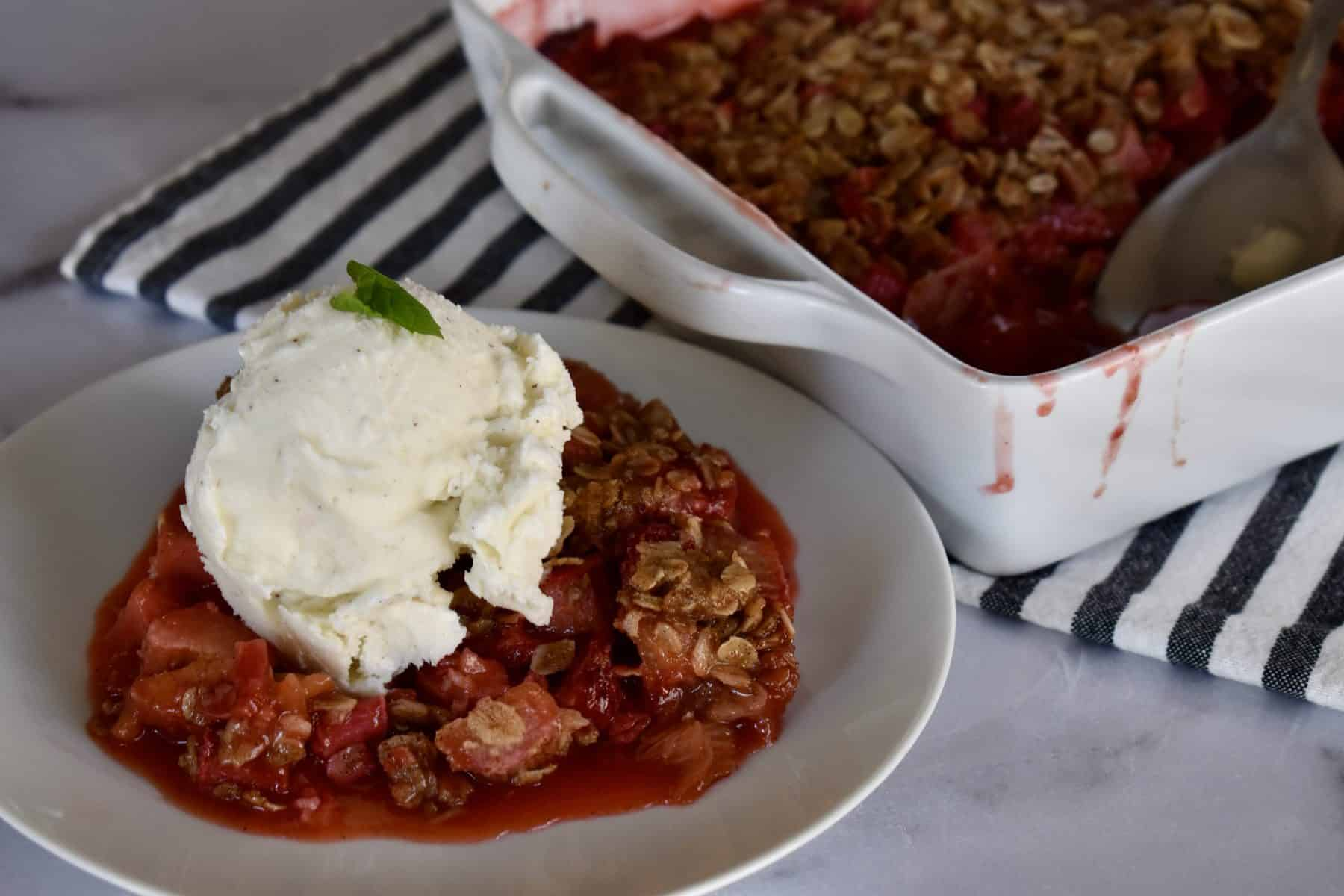 Strawberry Rhubarb Crisp on a white plate with a white serving dish behind it.