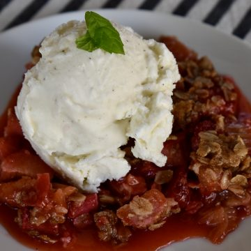 Strawberry Rhubarb Crisp on a white plate with a scoop of vanilla ice cream on top.