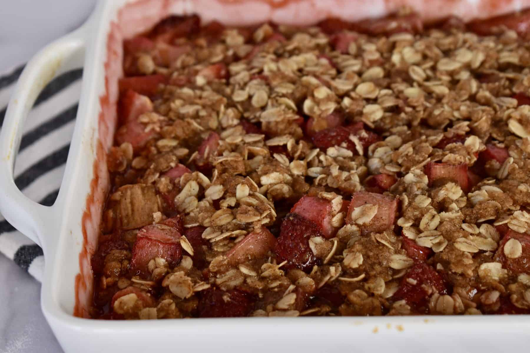 Strawberry Rhubarb Crisp that has been baked in a white baking dish.