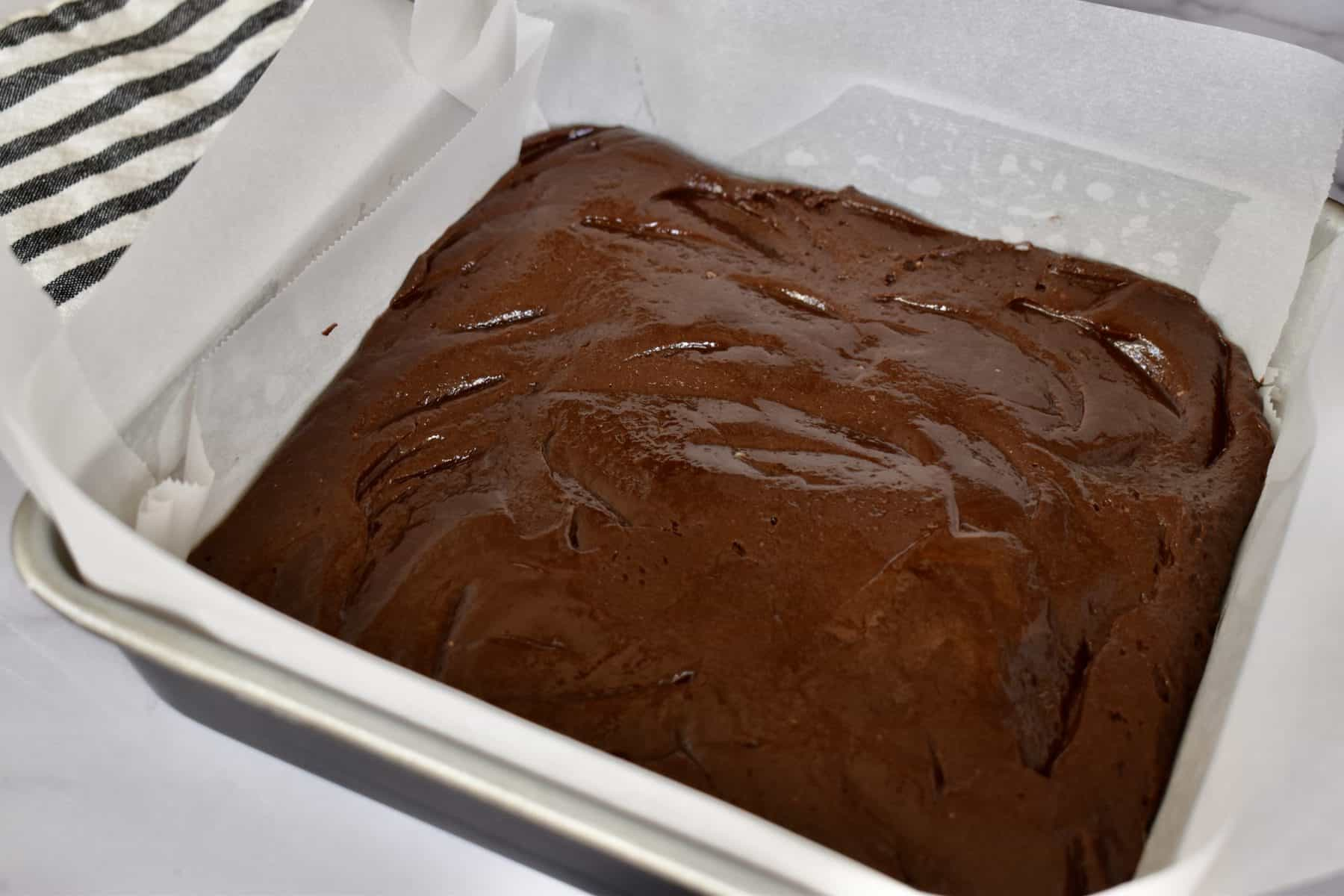 Brownie Batter in a lined baking pan.